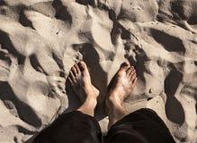 Pares de pies en la arena de la playa Fotos de archivo libres de regalías