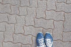 Pares de pies pateados azules en piedras de pavimentación modeladas Imagen de archivo
