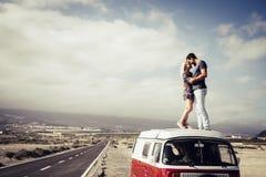 Pares de povos caucasianos do homem e da mulher no amor que está sobre o telhado de uma camionete clássica vintage que beija e qu foto de stock