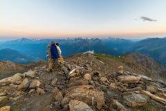 Pares de povos que olham o nascer do sol sobre o pico de montanha de Mont Blanc 4810 m ` Aosta de Valle d, aventuras italianas do Imagens de Stock Royalty Free