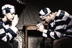 Pares de prisioneiros que sentam-se perto da tabela de cabeceira e que rezam na Fotografia de Stock Royalty Free