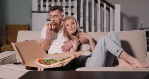 Pares de relajación en el amor que comparte la rebanada de la pizza metrajes