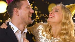 Pares de risa alegres que se divierten en la fiesta de cumpleaños, partido-ventilador que sopla masculino metrajes