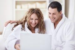 Pares de risa con la computadora portátil Imagen de archivo libre de regalías