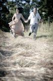 Pares de risa indios hermosos jovenes que corren en campo con las rosas blancas Imagen de archivo libre de regalías