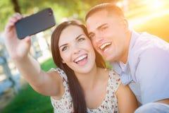 Pares de risa de la raza mixta que toman el autorretrato con un teléfono elegante Foto de archivo