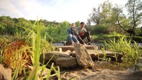 Pares de risa que se sientan en el puente de madera al aire libre metrajes