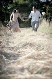 Pares de riso do indiano considerável novo que correm no campo com rosas brancas Fotos de Stock