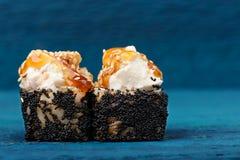 Pares de rolos de sushi com molho do queijo creme e do caramelo no preto Imagens de Stock Royalty Free