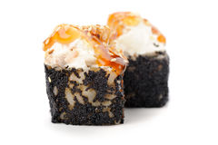 Pares de rolos de sushi com molho do queijo creme e do caramelo no preto Fotografia de Stock Royalty Free