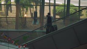 Pares de sócios comerciais que movem sobre a escada rolante no aeroporto, chegando para encontrar-se filme