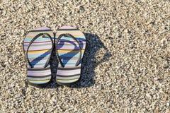 Pares de sandalias de la playa que mienten en una playa fotografía de archivo libre de regalías