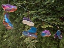 Pares de sapatas atadas com os laços que penduram no cabo foto de stock