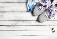 Pares de sapatas, de garrafa de água e de fones de ouvido do esporte na madeira branca Fotos de Stock