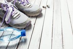 Pares de sapatas, de garrafa de água e de fones de ouvido do esporte na madeira branca Fotos de Stock Royalty Free