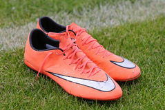 Pares de sapatas do futebol no campo de grama Imagem de Stock Royalty Free