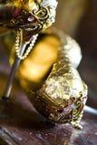Pares de sapatas douradas jeweled no interior antigo imagens de stock