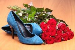 Pares de sapatas fêmeas azuis e grupo de rosas vermelhas Fotos de Stock Royalty Free