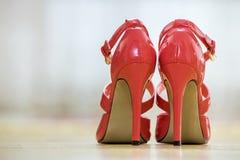 Pares de sapatas fêmeas do entalhe vermelho de couro elegante do salto alto com as curvaturas douradas isoladas no fundo claro do imagens de stock royalty free