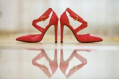 Pares de sapatas fêmeas do entalhe vermelho de couro elegante do salto alto com as curvaturas douradas isoladas no fundo claro do imagem de stock