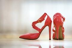 Pares de sapatas fêmeas do entalhe vermelho de couro elegante do salto alto com as curvaturas douradas isoladas no fundo claro do foto de stock