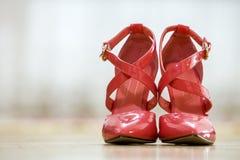 Pares de sapatas fêmeas do entalhe vermelho de couro elegante do salto alto com as curvaturas douradas isoladas no fundo claro do fotografia de stock