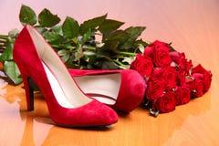 Pares de sapatas fêmeas vermelhas e grupo de rosas vermelhas Fotografia de Stock Royalty Free