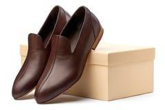 Pares de sapatas masculinas marrons na frente da caixa da mostra Foto de Stock