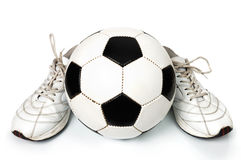 Pares de sapatilhas e de esfera de futebol fotografia de stock royalty free