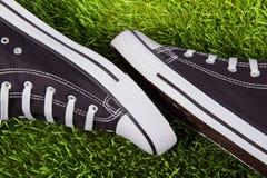 Pares de sapatilhas pretas na grama verde Imagens de Stock Royalty Free