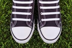 Pares de sapatilhas preto e branco no prado verde Imagens de Stock