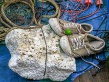 Pares de sapatilhas velhas na espuma branca com rede de pesca e de corda vermelha no barco de pesca fotografia de stock royalty free