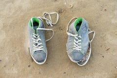 Pares de sapatos de ginástica velhos dos esportes em uma areia Imagem de Stock