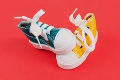 Pares de sapatos de ginástica da cor amarela e verde no papel vermelho Foto de Stock