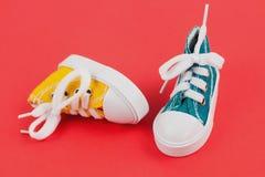 Pares de sapatos de ginástica da cor amarela e verde no papel vermelho Foto de Stock Royalty Free