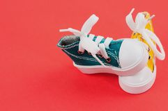 Pares de sapatos de ginástica da cor amarela e verde no papel vermelho Imagens de Stock Royalty Free