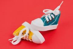 Pares de sapatos de ginástica da cor amarela e verde no papel vermelho Fotos de Stock