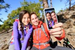 Pares de Selfie usando el teléfono elegante que camina en naturaleza Fotos de archivo libres de regalías