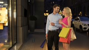 Pares de shopaholics que andam ao longo da rua da compra que olha o disconto e a venda filme