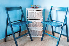 Pares de sillas de madera azules y de pequeña cómoda blanca cerca de la pared Imagenes de archivo