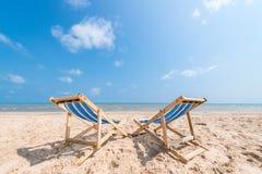 Pares de sillas en la playa arenosa el día soleado que busca el azul imagenes de archivo