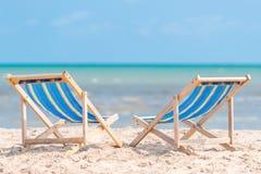 Pares de sillas en la playa arenosa el día soleado que busca el azul fotos de archivo