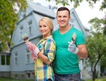 Pares de sorriso com as escovas de pintura sobre a casa Imagens de Stock