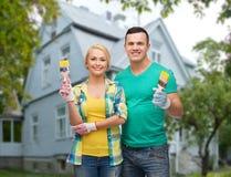 Pares de sorriso com as escovas de pintura sobre a casa Imagem de Stock Royalty Free
