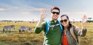 Pares de sorriso com as trouxas que viajam em África foto de stock