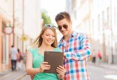 Pares de sorriso com o PC da tabuleta na cidade Imagens de Stock