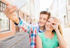 Pares de sorriso com o smartphone na cidade Imagens de Stock Royalty Free