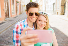 Pares de sorriso com o smartphone na cidade Imagem de Stock Royalty Free