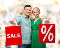 Pares de sorriso com sacos de compras Fotografia de Stock Royalty Free