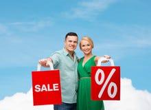 Pares de sorriso com sacos de compras Imagem de Stock Royalty Free